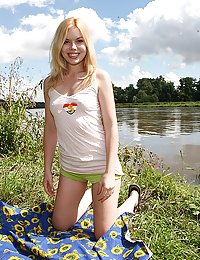Naked and horny teenager masturbates near a lake using a toy